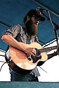 Foto von William Fitzsimmons mit Gitarre und Cap